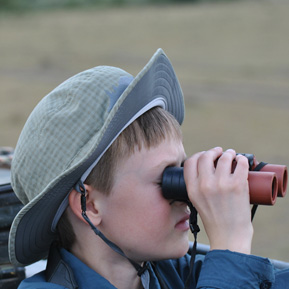 Photo of a Boy looking through Binoculars